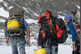 Glaciologues acheminant sur le glacier de Gébroulaz le matériel pour la pose de balises de mesure de la variation d'épaisseur de la couche supérieure de glace.