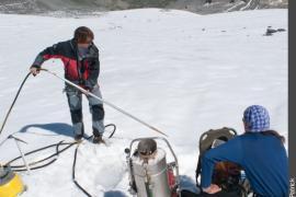glaciologues retirant la sonde à vapeur de la glace, avant d'y introduire une balise en bois de 4 segments de 2 mètres.